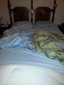 Messy bed with two flat sheets